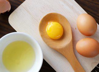Желток в деревянной ложке возле яиц