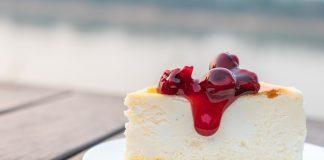 Классический чизкейк на белой тарелке, на деревянной поверхности