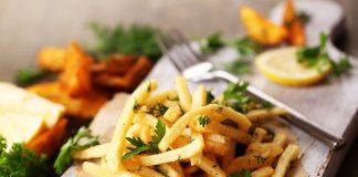 Картофель фри с зеленью на досточке с вилкой