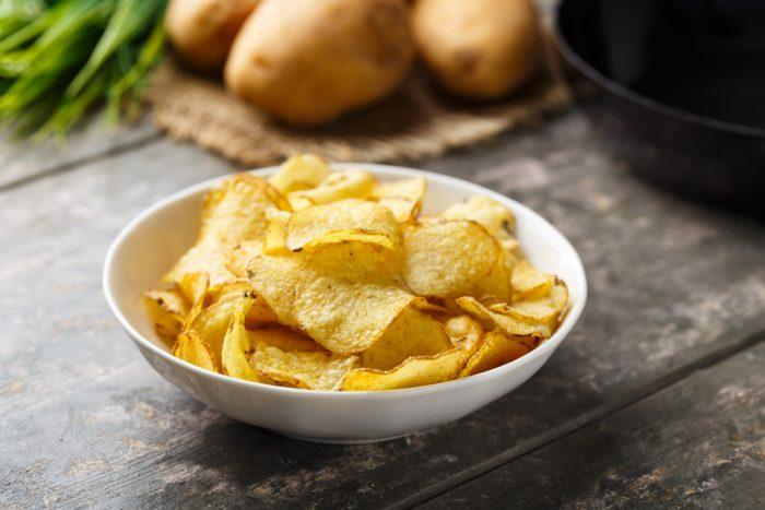 Картофельные чипсы в белой тарелке