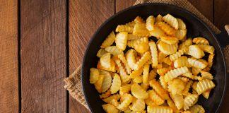 Картофель в сковороде на деревянной поверхности