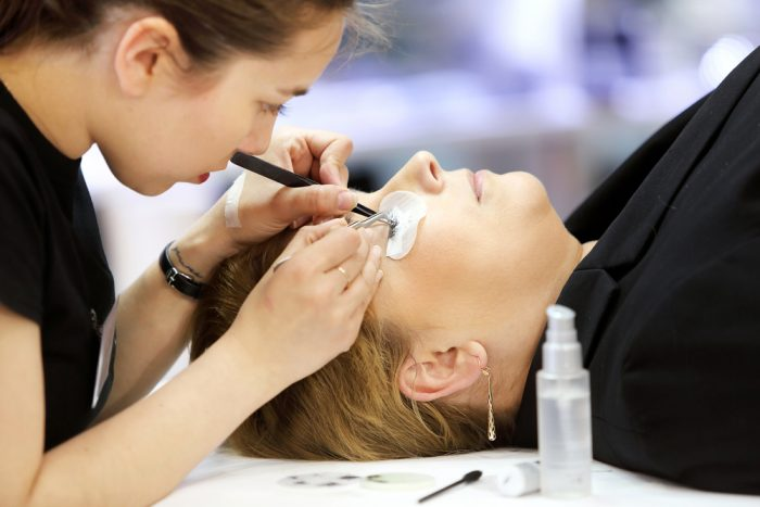 Косметолог наращивает ресницы женщине
