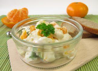 Салат в прозрачной тарелке на досточке на фоне мандарин