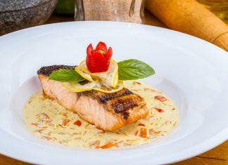 Филе лосося в тарелке украшенное лимоном и помидором в виде цветка