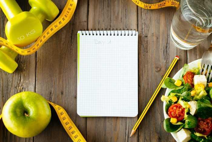 Блокнот с карандашом лежит возле яблок, салата, сантиметра и гирек
