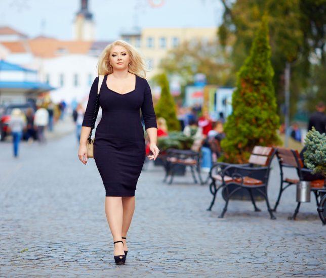 Девушка в черном платье по колено идет по городу