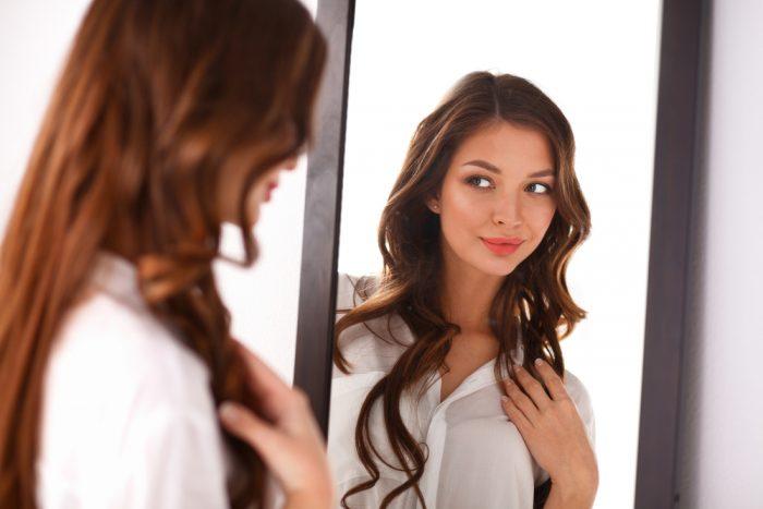 Девушка в белой рубашке смотрит в зеркало