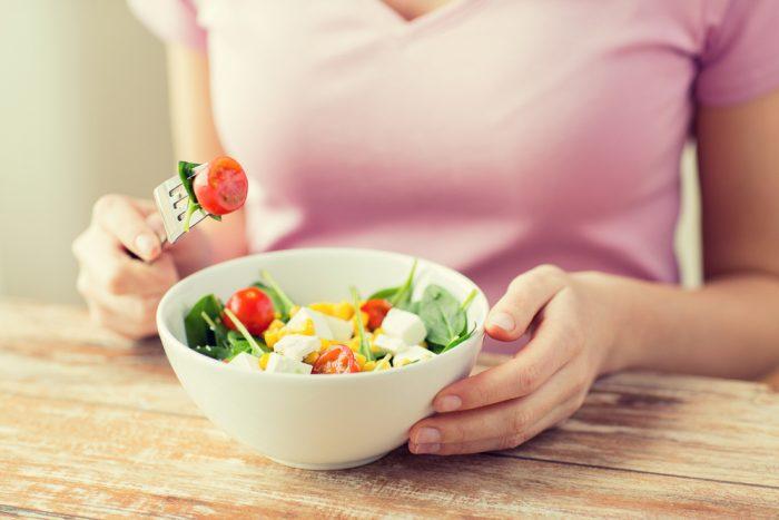 Девушка в розовой кофте ест салат