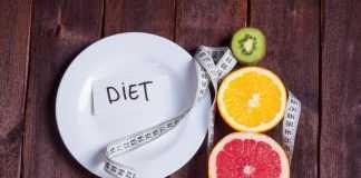 Половина грейпфрута, апельсина и киви возле белой тарелки с сантиметром