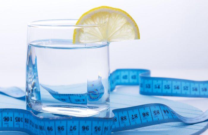 Голубой сантиметр возле стакана воды с лимоном