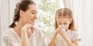 Девочка возле мамы пьет молоко