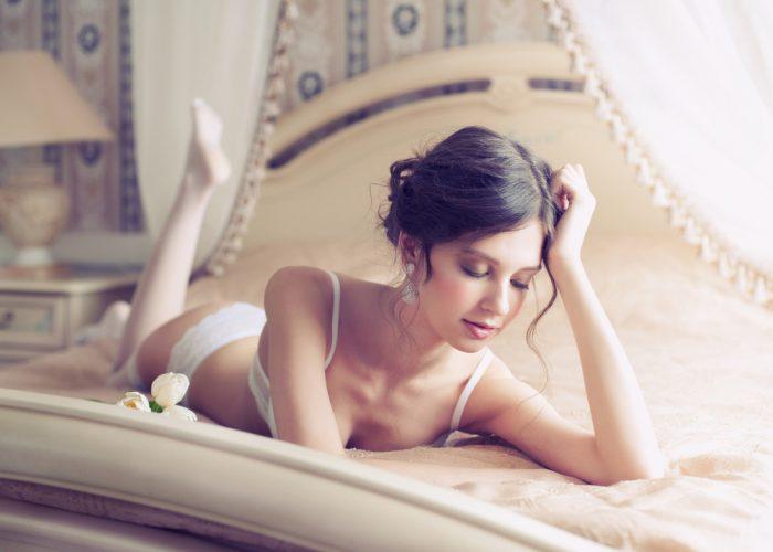 Девушка лежит на кровати в белом белье