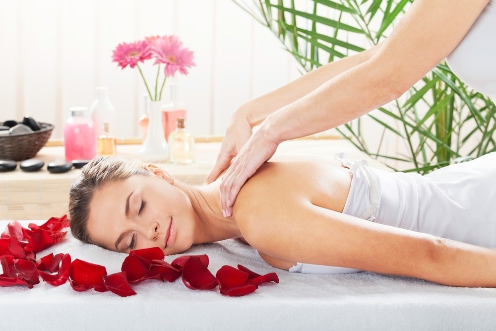 Девушка на массаже в лепестках роз