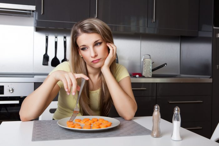 Девушка перед тарелкой с морковкойзадумалась