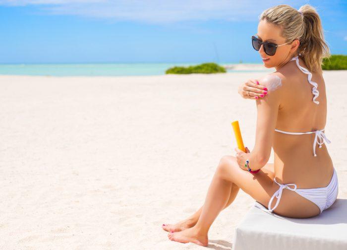 Девушка в белом купальнике сидит на пляже и наносит крем на плеже