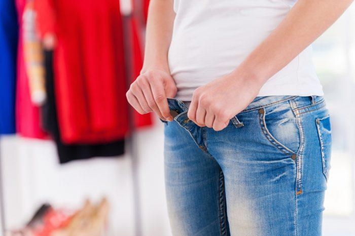 Девушка в белой майке застегивает на себе джинсы