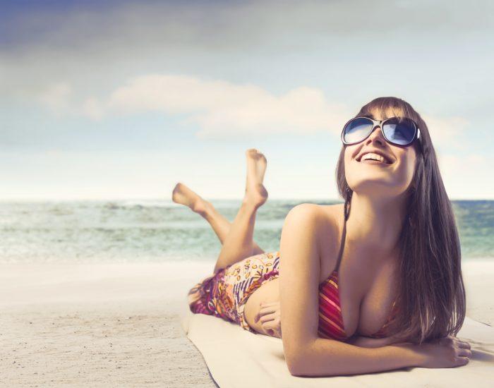 Девушка лежит в купальнике, в очках на пляже