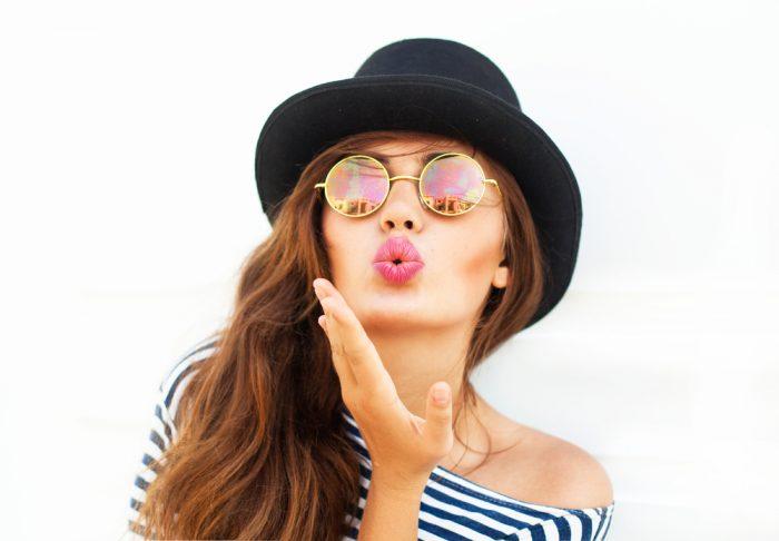 Девушка в полосатой кофте,черной шляпе и в очках посылает воздушный поцелуй