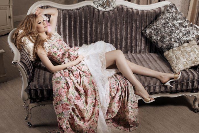 Девушка в длинном пышном платье лежит на диване