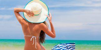 Девушка в белом купальнике,вшлпке с полосатой сумкой на пляже