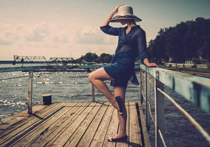 Девушка в тунике и в шляпе у реки