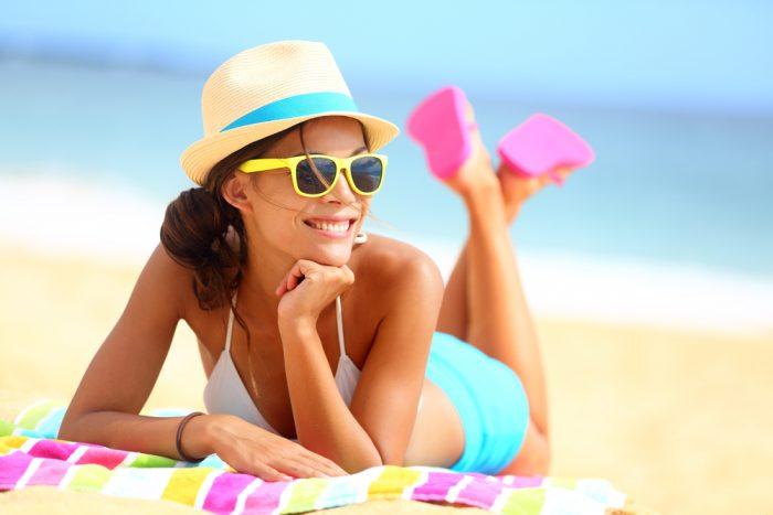 Девушка на пляже лежит в шляпке, очках на полотенце