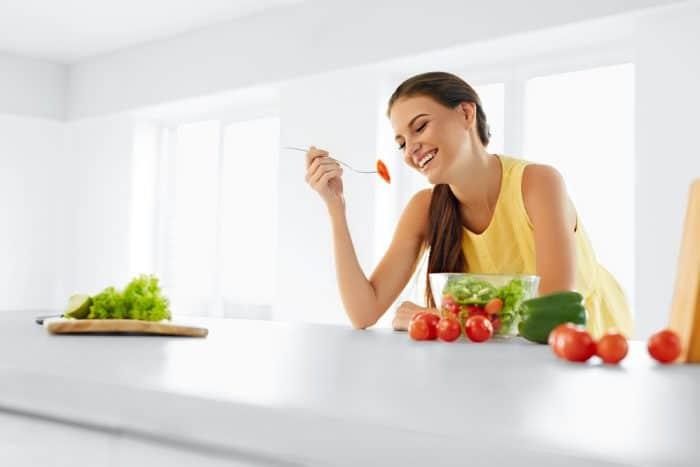 Девушка за белым столом ест помидор