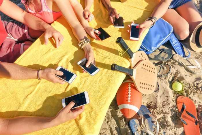 На пляже , на желтом полотенке много рук с мобильными телефонами