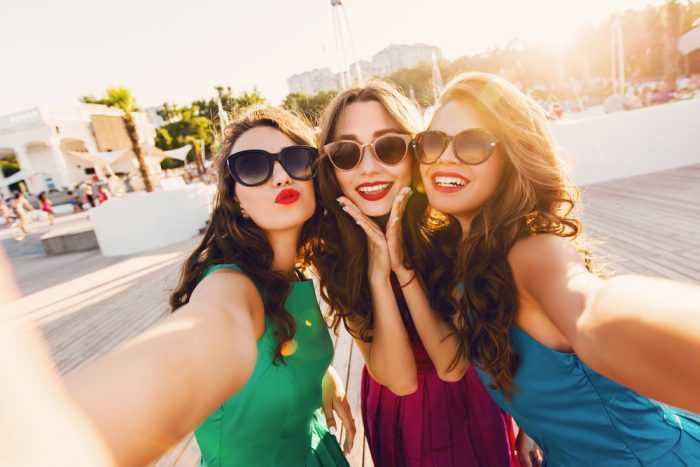 Три подруги делают селфи в очках