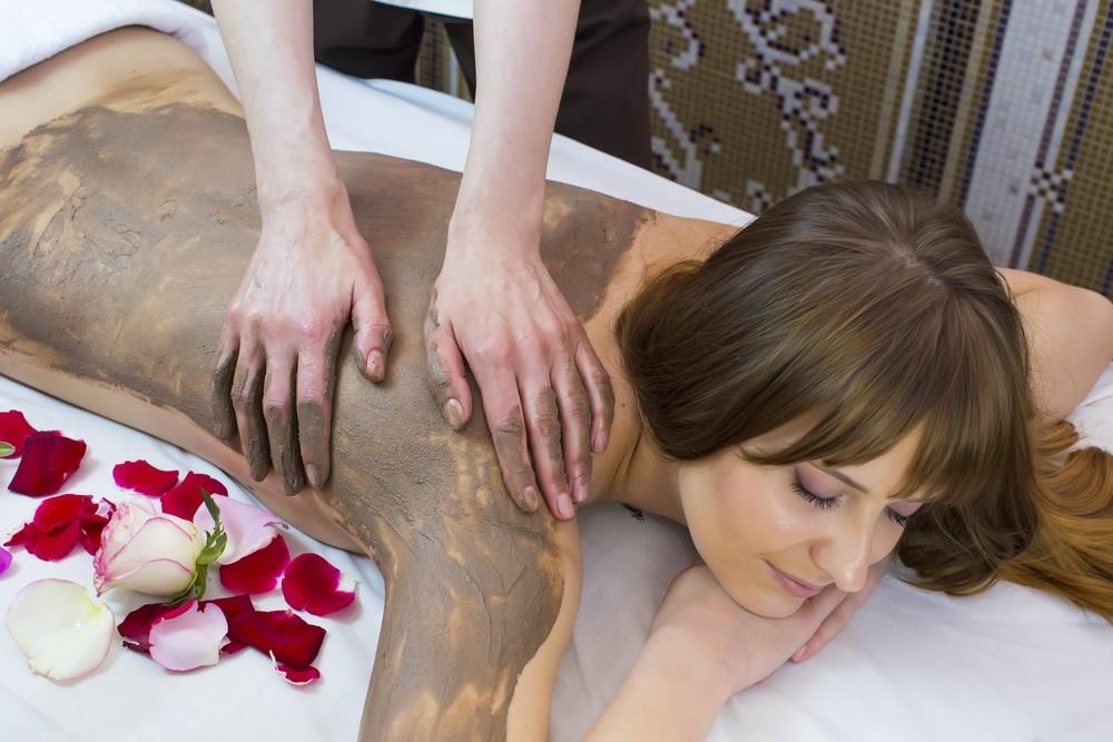 женщине в спа наносят скраб на спину
