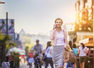 Девушка в серой юбке с портфелем идет по городу
