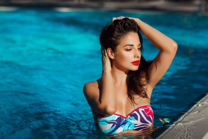 девушка в купальнике и с красной помадой в бассейне