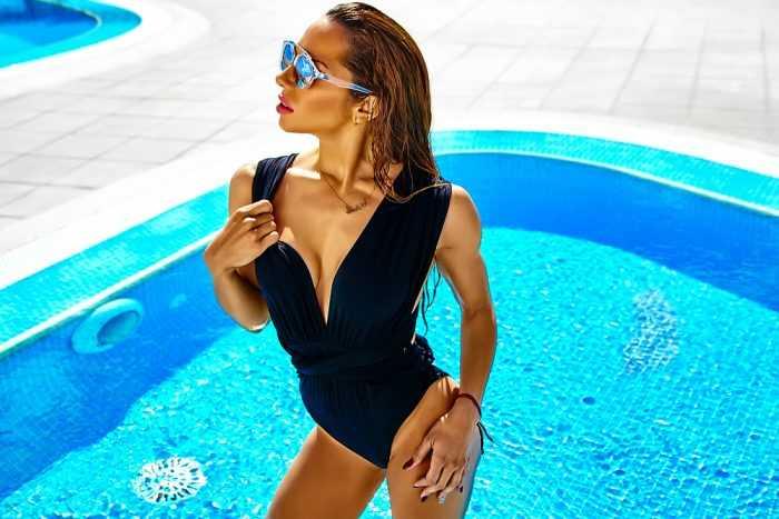 Девушка в очках и в черном закрытом купальнике у бассейна