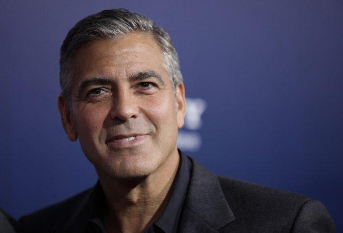 Джордж Клуни на синем фоне улыбается