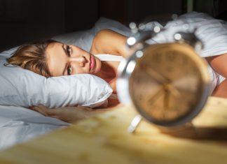 Девушка лежит в постели и смотрит на часы