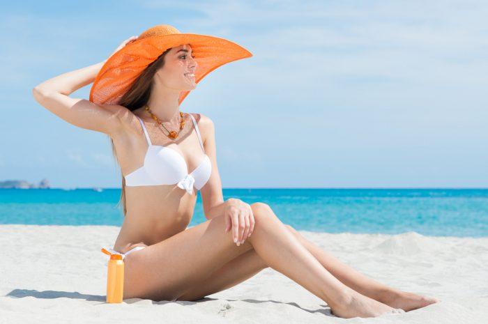 Девушка на пляже в белом купальнике и оранжевой шляпе