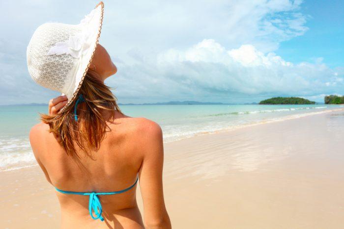 Девушка в белой шляпке идет по пляже