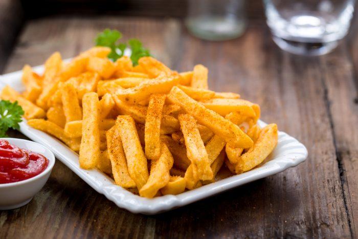 Картофелдь фри на тарелке возле соуса