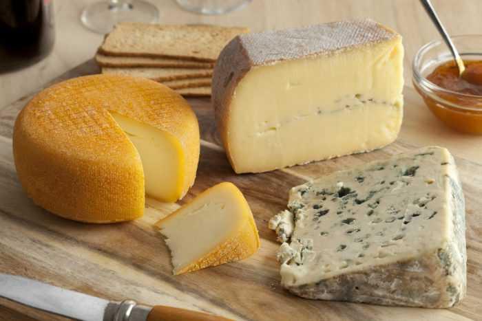 Разные виды сыра на деревянной поверхности