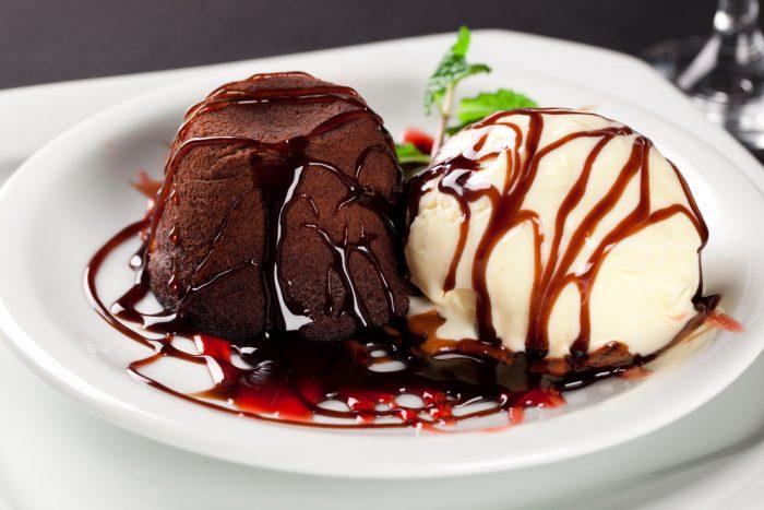 Шоколадный десерт с мороженым на белой тарелке