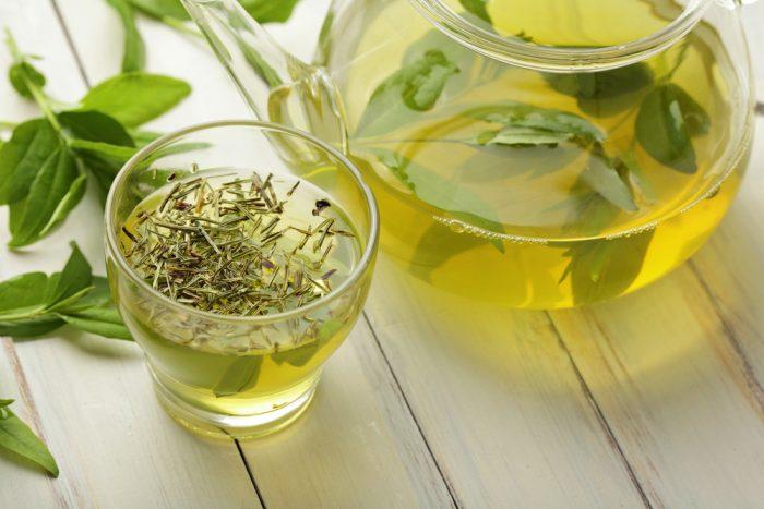 Зеленый чай в чашке и чайничке с листочками на столе