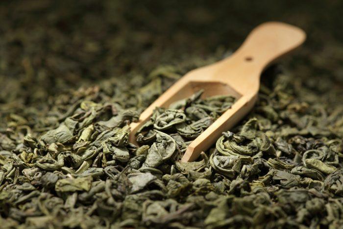 Листья зеленого чая с деревянной лопаткой