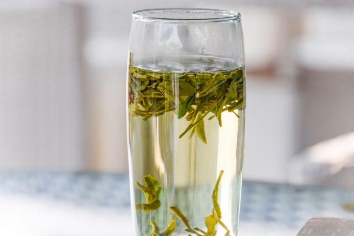 Зеленый чай с листьями в стакане
