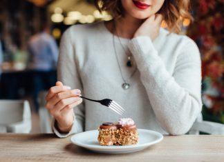 Девушка ест десерт в кафе
