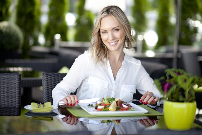 Девушка ест салат в кафе