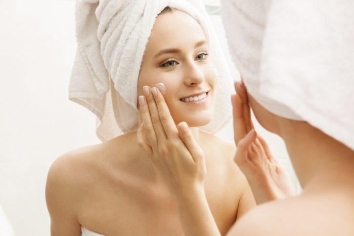 Девушка с полотенцем на голове мажет лицо кремом