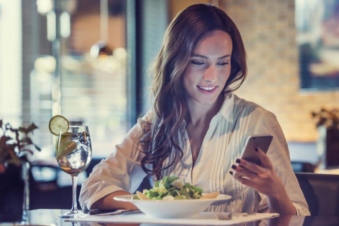 Девушка сидит перед салатом и бокалом воды и смотрит в телефон