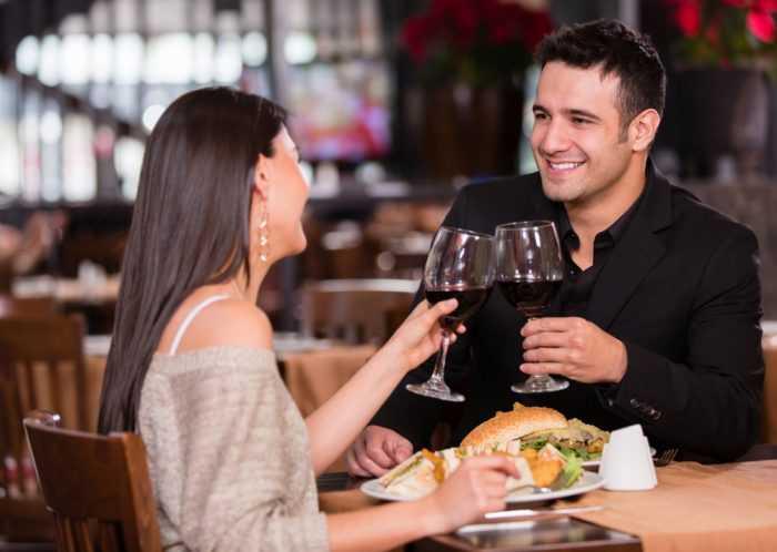 Парень с девушкой с бокалами вина обедают в ресторане