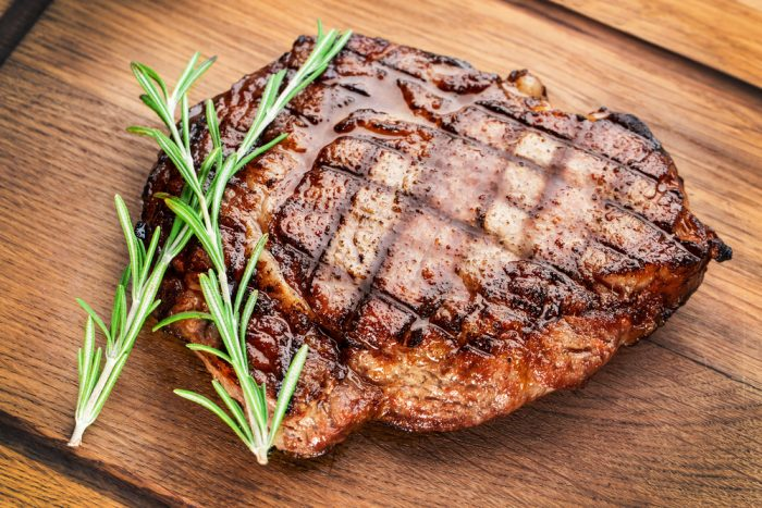 Мясо с гриля на досточке с веточкой розмарина