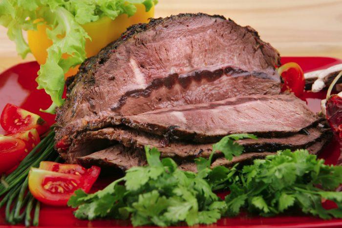 Запеченное мясо на терелке с листьями салата и помидорами